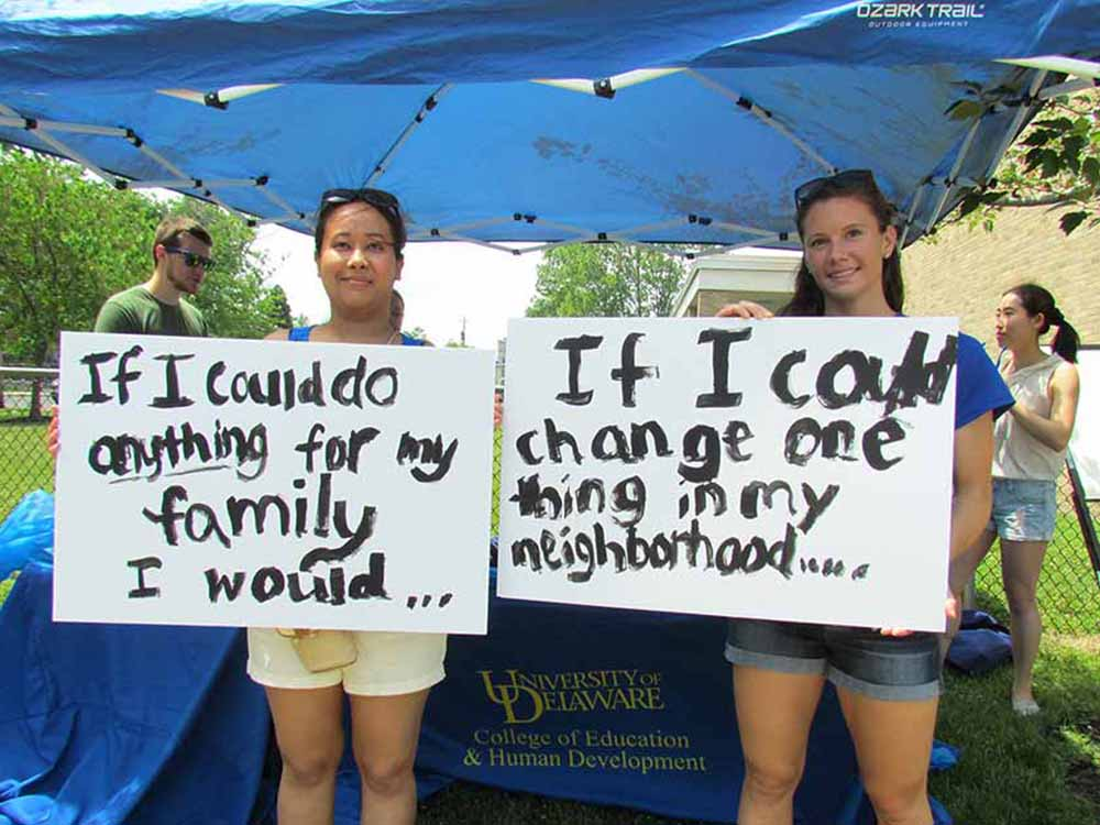 Students holding handwritten signs at a UDel event