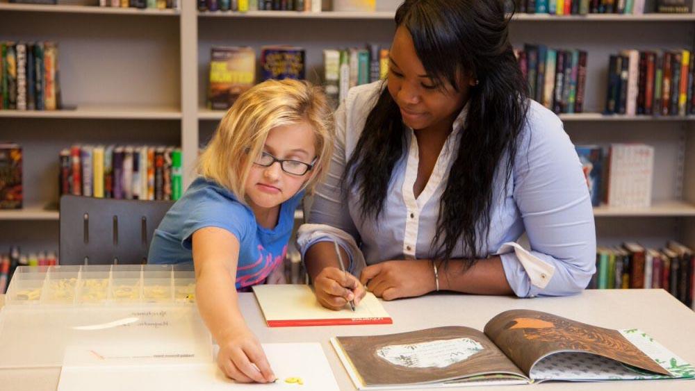 A woman teaching a young girl